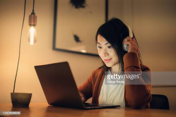 young woman remote learning at home with laptop - using laptop stock pictures, royalty-free photos & images