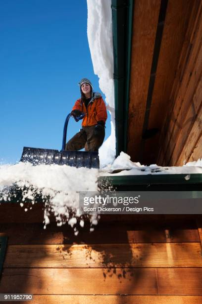a young woman removes snow from the roof of her house - home run ストックフォトと画像