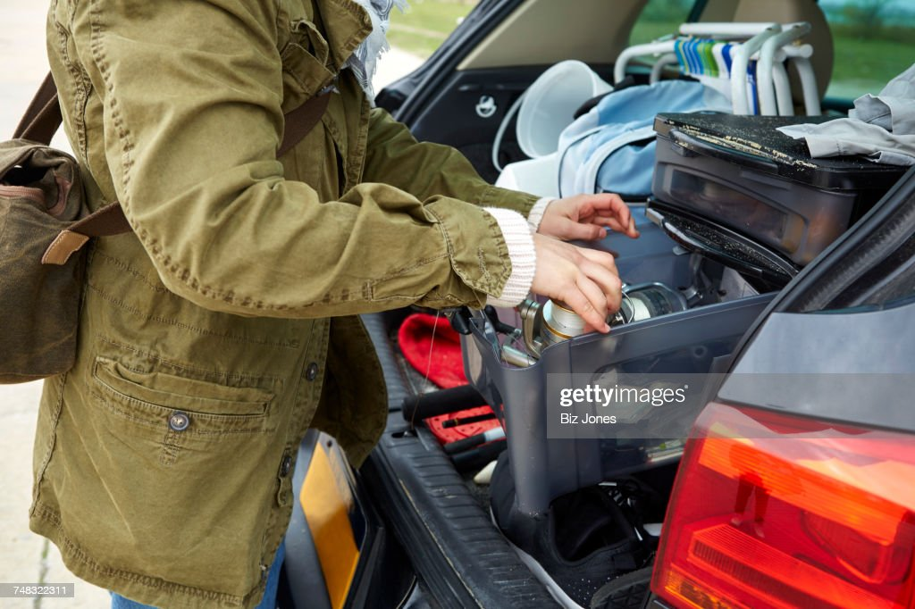 Young woman removing belongings from boot of car, mid section : Stock Photo