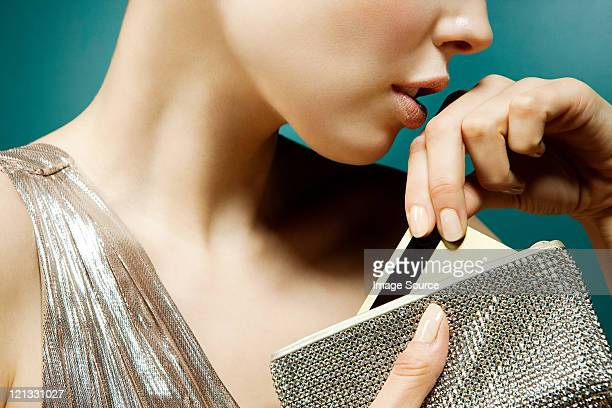 Young woman removing credit card from purse