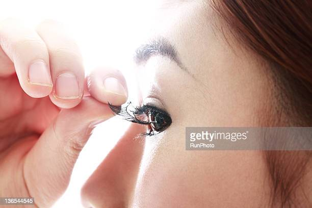 young woman removing false eyelash
