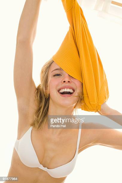 Young woman removing jumper, obscuring face