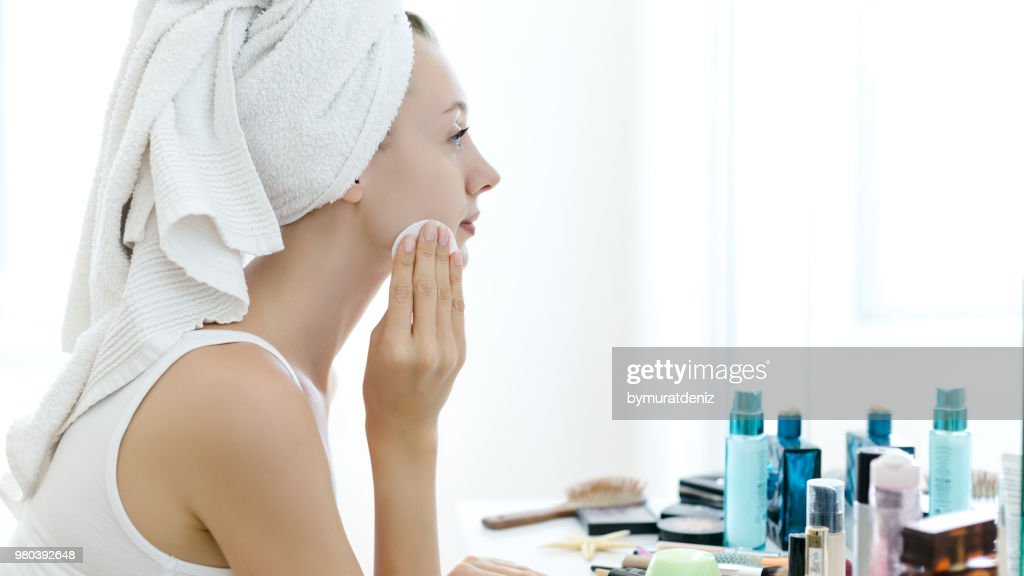 Young woman removing makeup from her face : Stock Photo