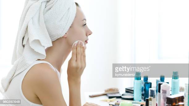 young woman removing makeup from her face - stage make up stock photos and pictures