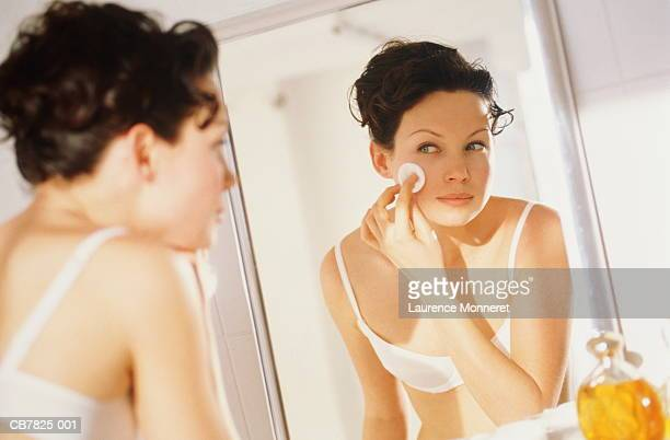 Young woman removing make-up, looking in mirror