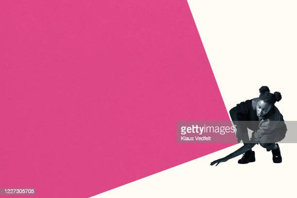 young woman removing something from below block - searching stock pictures, royalty-free photos & images