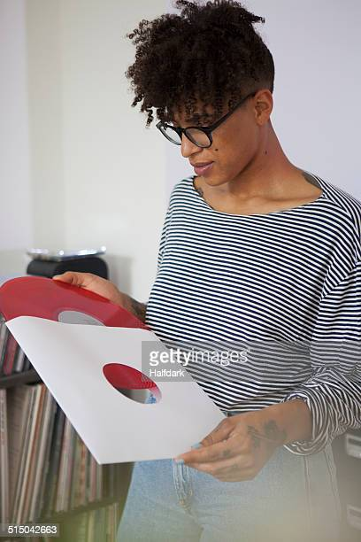 Young woman removing vinyl record from paper sleeve at home