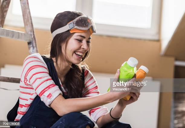 Young woman renovating her new home, holding bottles of paint