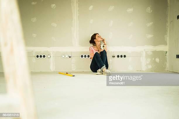 Young woman renovating sitting at blank wall