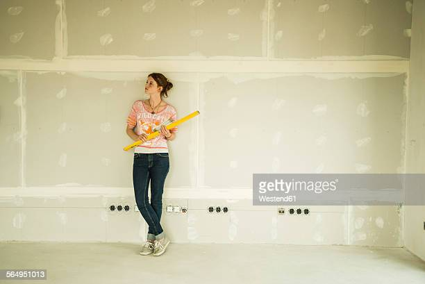 Young woman renovating standing at blank wall