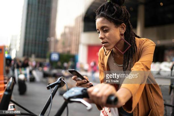 young woman renting shared bicycle in city centre - sharing economy stock pictures, royalty-free photos & images