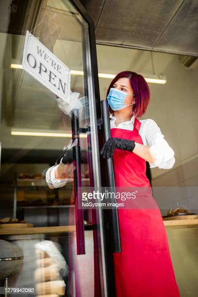 young woman reopening her bakery during corona virus - reopening stock pictures, royalty-free photos & images