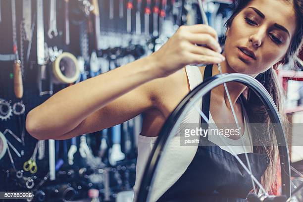 Young woman repairing a bike