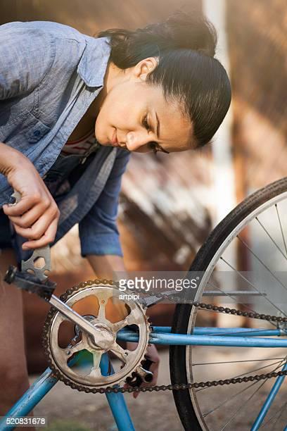 Junge Frau reparieren ein Fahrrad