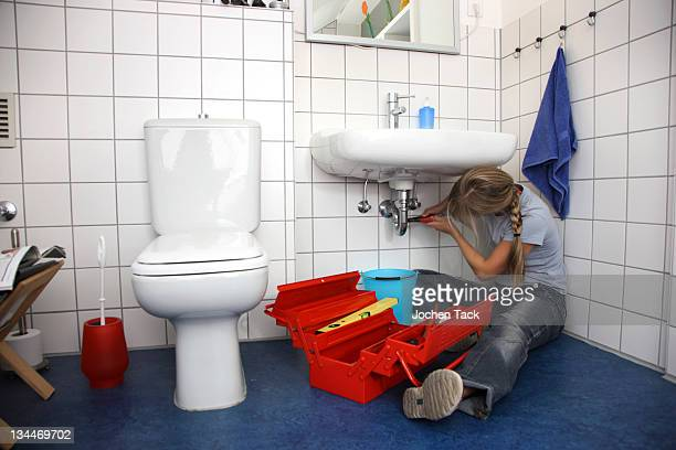 Young woman repairing a defective water faucet in a bathroom