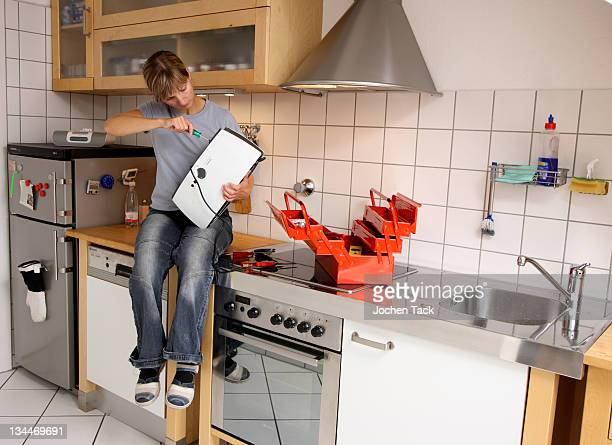 Young woman repairing a toaster in the kitchen