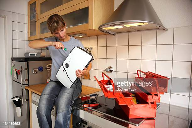 young woman repairing a toaster in the kitchen - toaster appliance stock pictures, royalty-free photos & images