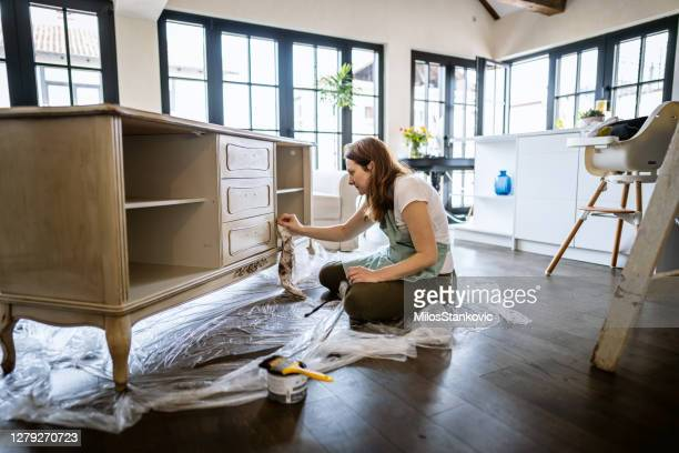 young woman repairing an old furniture and enjoying at home - furniture stock pictures, royalty-free photos & images