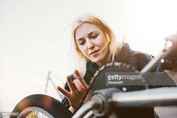 Young woman repairing BMX bicycle
