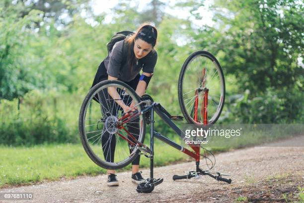 young woman repairing her bicycle - flat tire stock pictures, royalty-free photos & images