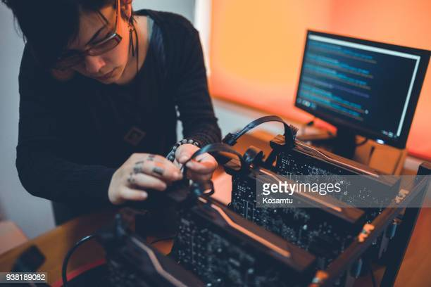 young woman repairing rig and checking the cables - blockchain stock pictures, royalty-free photos & images