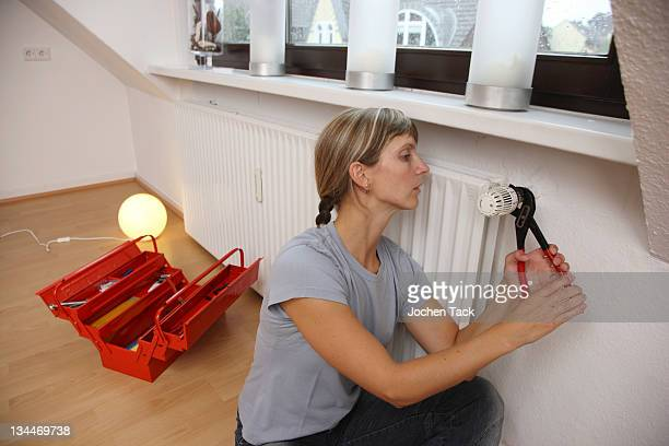 young woman repairing the thermostat of a radiator - spoil system stock pictures, royalty-free photos & images