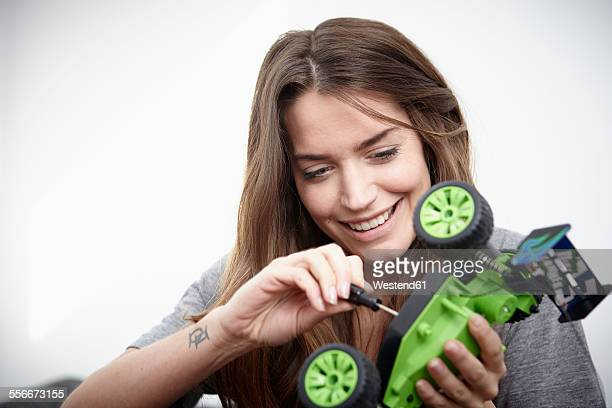 Young woman repairing toy car