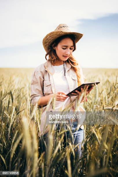 Young woman researcher checking cultivated wheat field with digital tablet
