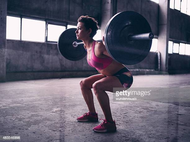 young woman resting a heavy barbell on her shoulders - barbell stock pictures, royalty-free photos & images