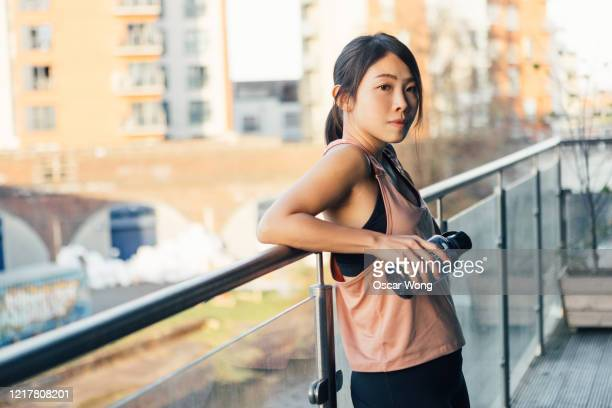 young woman resting after doing exercise on the balcony - leaning stock pictures, royalty-free photos & images