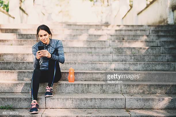 young woman resting after jogging in the park - pauze nemen stockfoto's en -beelden