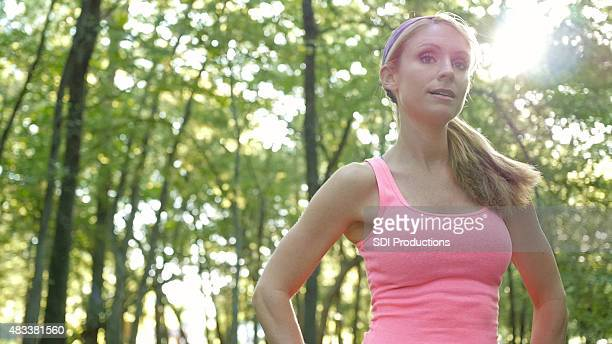 Young woman resting after running off road in sunny park