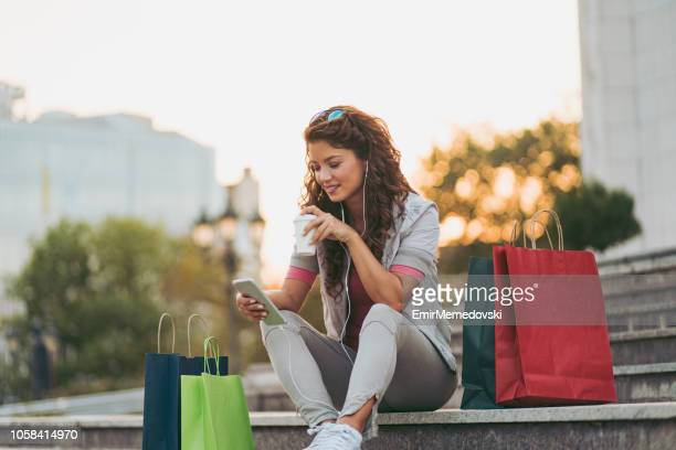 young woman resting after shopping and listening to music - spending money stock pictures, royalty-free photos & images