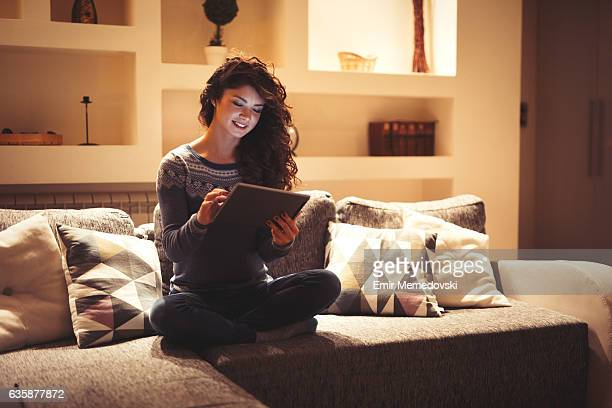 Young woman resting at home and using digital tablet.