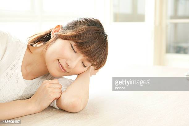 Young woman resting by table, smiling