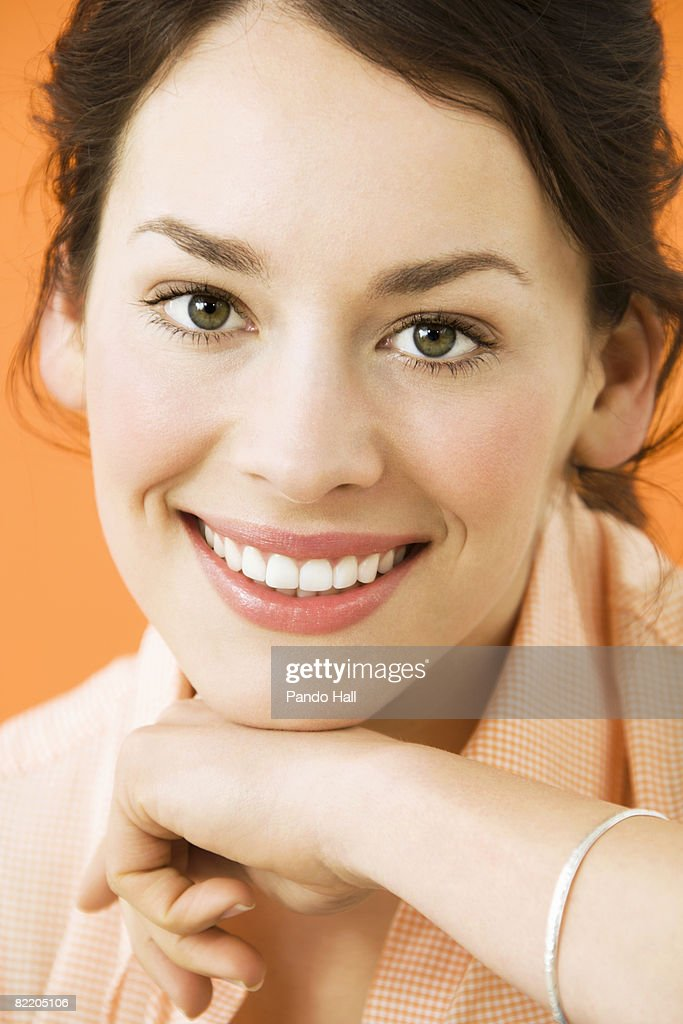 Young woman resting chin on arm, smiling, portrait : Stock Photo