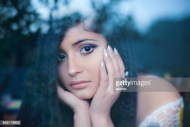 young woman resting chin on hand and looking at camera. - hand on chin stock pictures, royalty-free photos & images