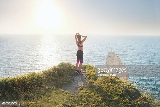 Young woman resting during jog on edge of cliff