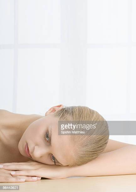 Young woman resting head on arms