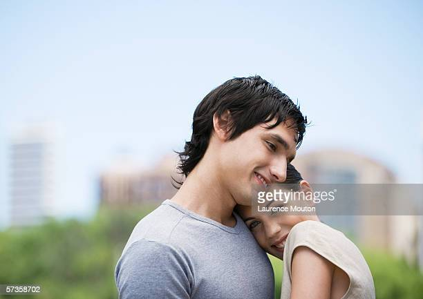 Young woman resting head on boyfriend's shoulder