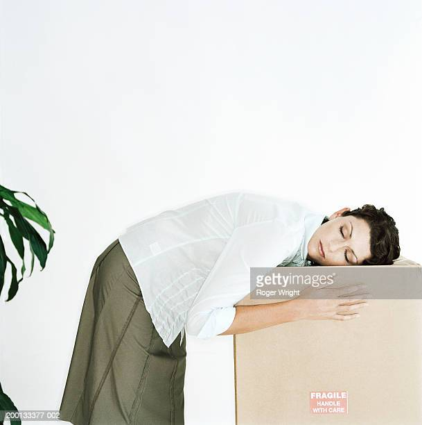 young woman resting head on large cardboard box, eyes closed - overworked stock pictures, royalty-free photos & images