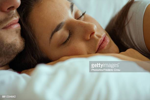 Young woman resting in bed with partner