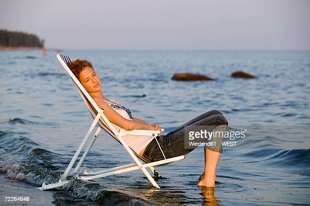 young woman resting in deck chair on beach, side view - rolled up trousers stock pictures, royalty-free photos & images