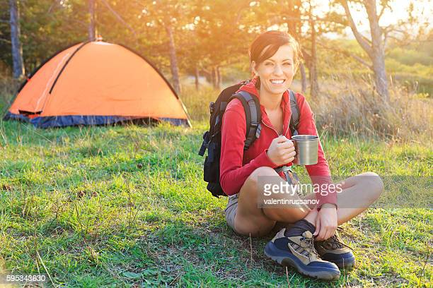 Young woman resting in front of a tent