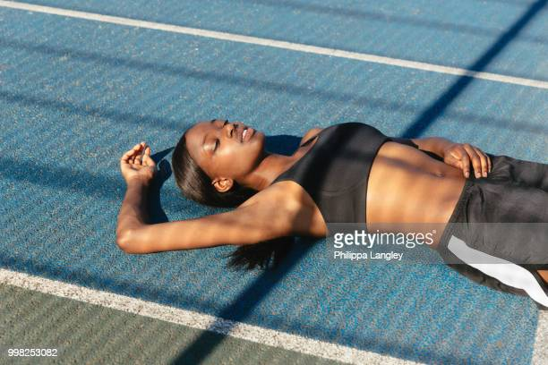 young woman resting in sports court - crop top stock pictures, royalty-free photos & images