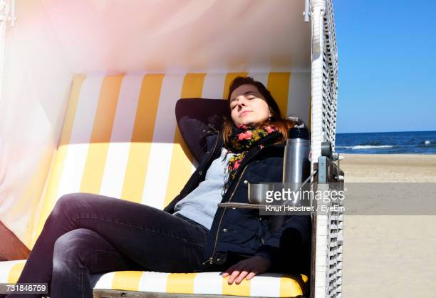 Young Woman Resting In Yellow Hooded Beach Chair On Sea Shore During Sunny Day