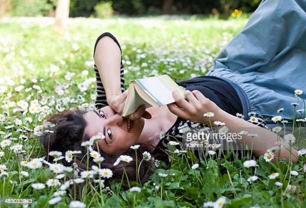 young woman resting on bloomy meadow