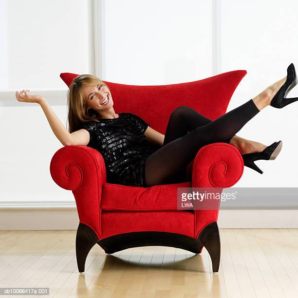 Young woman resting on chair, laughing, portrait