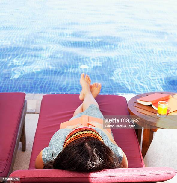 Young Woman Resting on Deck Chair by Pool