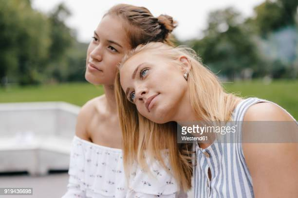 Young woman resting on female friend's shoulder